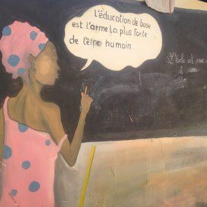 Malerei an Schultafel, Frau mit Sprechblase: L'éducation de base est l'arme la plus forte de l'être humain