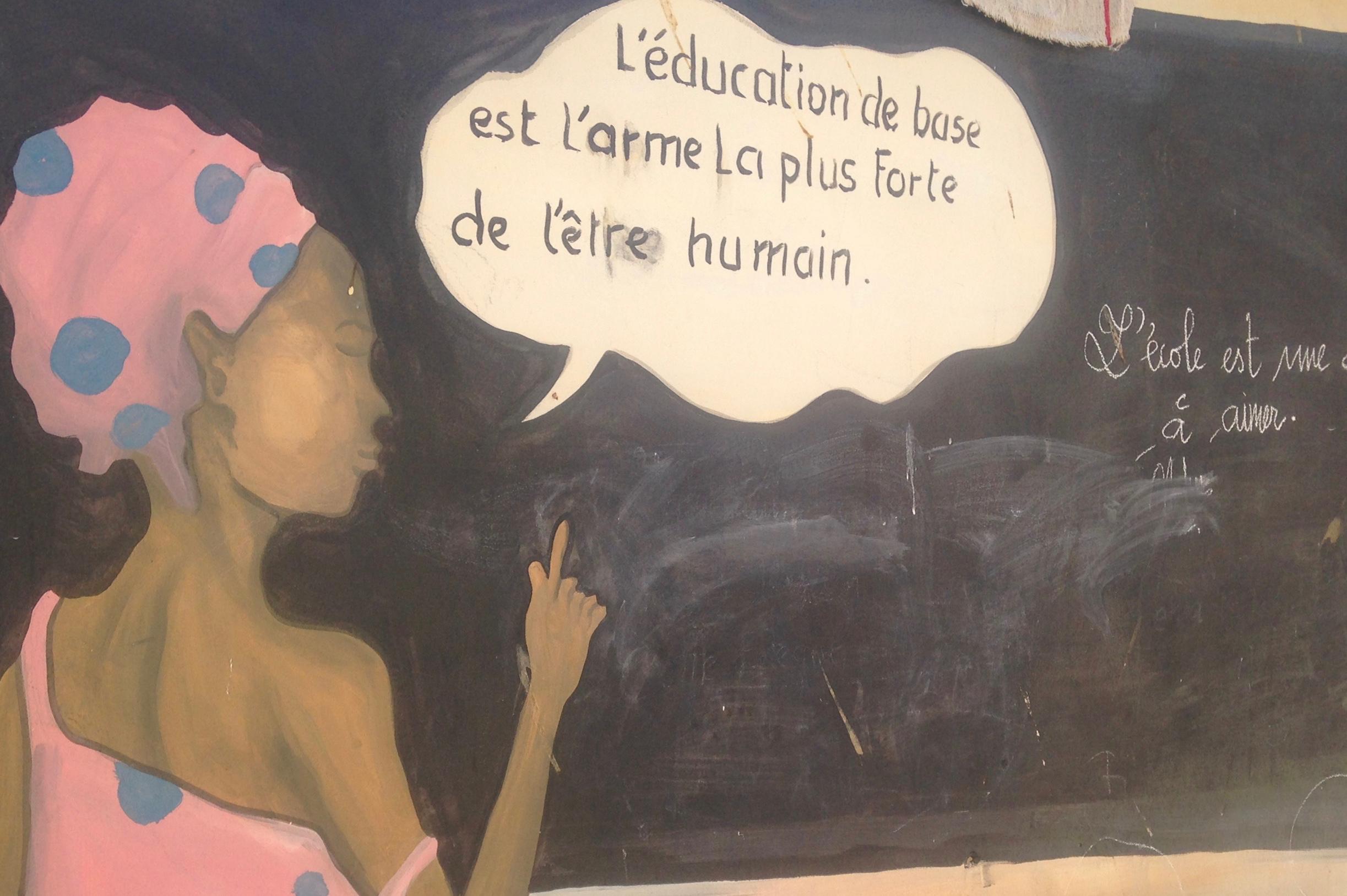 """gemaltes Veranstaltungsfoto: Frau vor Schultafel mit Sprechblase """"L'éducation de base est l'arme la plus forte de l'être humain"""""""