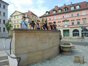Workshopteilnehmende mit verbundenen Augen auf Empore hinter einem Brunnen, lauschend