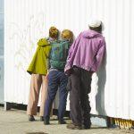 Drei Menschen lauschen an einer Wand